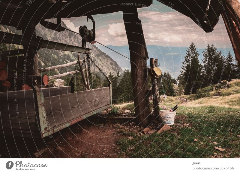 Goods cable car on the alpine pasture - view into the valley of the Alps - wooden shelter as protection against the weather - the material carrier for the supply of the farm in the mountains is made of wood