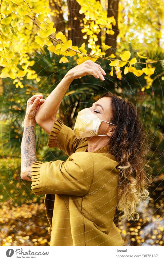 woman in yellow dress and mask in a park retouching hair garden yellowish leafs lifestyle mature portrait one people tree coat yellow overcoat scene romantic