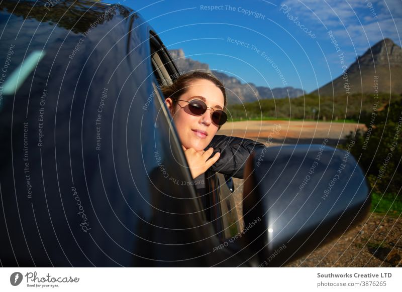 Young Woman On Road Trip Vacation Leaning Out Of Rental Car Window With Mountain Landscape Behind car rental road trip woman car hire young women holiday