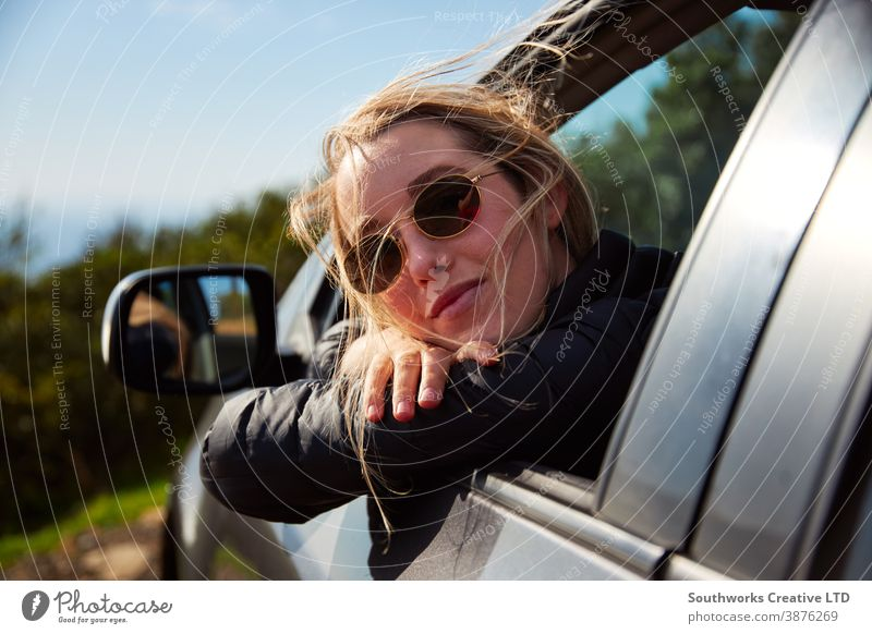 Young Woman On Road Trip Vacation Leaning Out Of Rental Car Window With Mountain Landscape Behind road trip car hire vacation holiday woman young women driving
