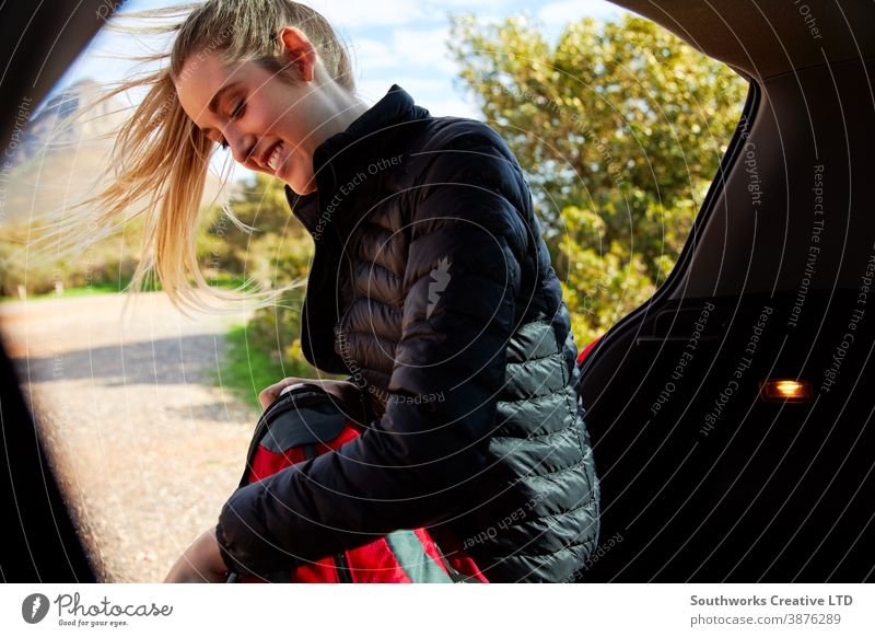 Woman In Open Tailgate Of Car Putting Thermos Flask In Backpack Ready For Hike In Countryside backpack walking hiking trek woman young women hike active packing
