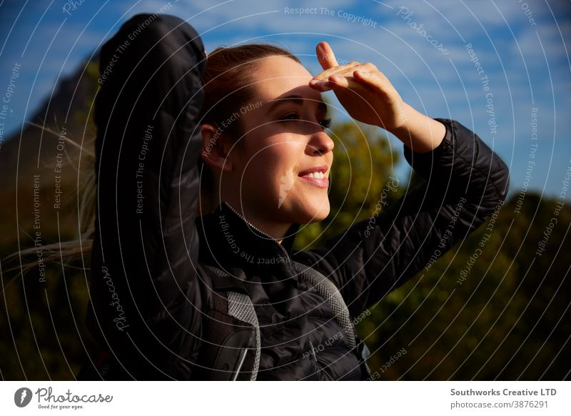Active Young Woman Hiking In Countryside Shielding Her Eyes From The Sun staycation travelling woman young women hike hiking walk walking trek active backpack