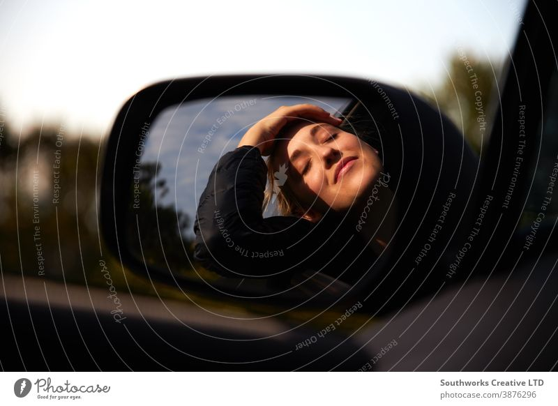 Reflection In Driving Mirror Of Young Woman On Road Trip Vacation Leaning Out Of Rental Car Window road trip car car hire woman young women holiday vacation