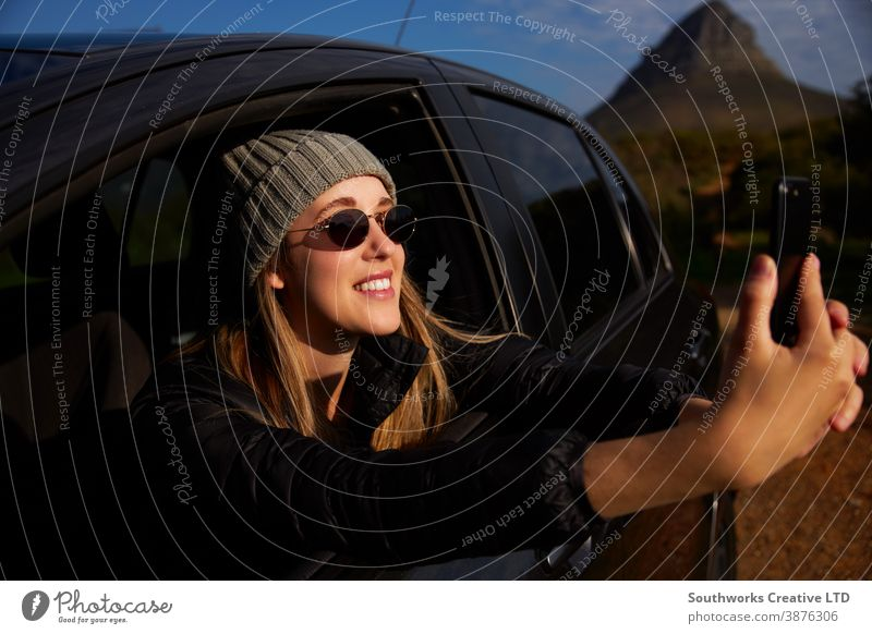 Young Woman On Road Trip Vacation Taking Photo Out Of Rental Car Window On Mobile Phone road trip vacation woman young women holiday car driving driver car hire