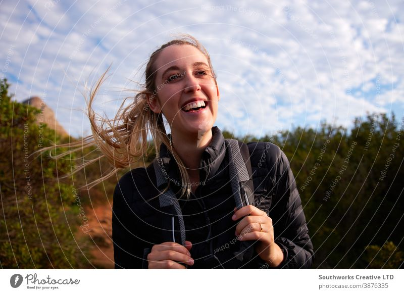 Portrait Of Young Woman With Backpack Hiking Along Path Through Countryside smiling woman young women hike hiking walk walking trek active backpack holiday