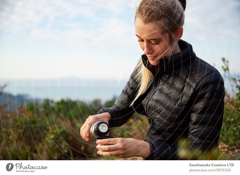 Young Woman Taking A Break From Countryside Hike And Pouring Coffee From Flask hike walking woman young women hiking trek camping taking a break pouring drink