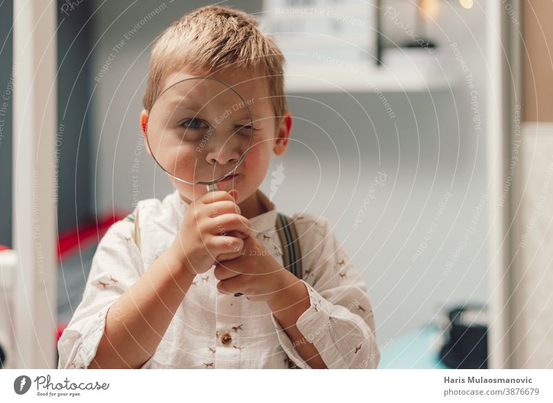Cute little boy holding a magnifying glass beautiful care caucasian child childhood concept curiosity curious curious boy cute education face find finding a job