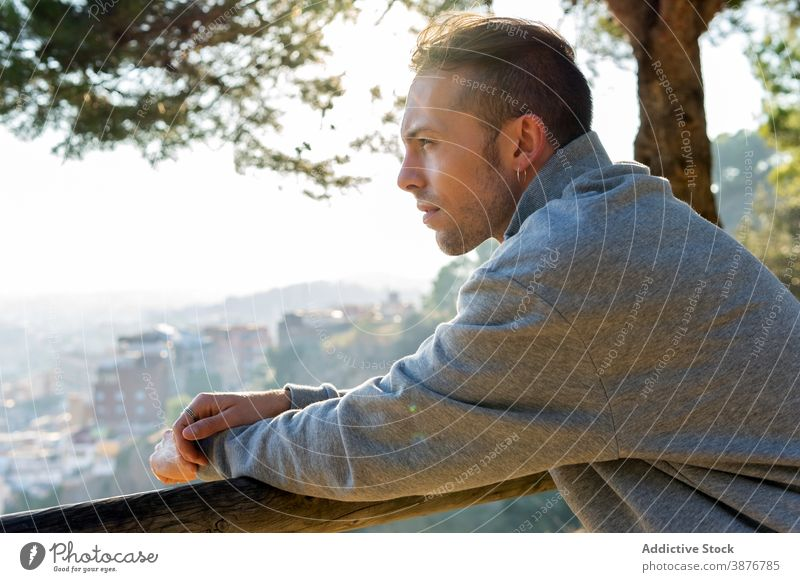 Thoughtful man resting on hill near city thoughtful pensive hipster contemplate dream think nature casual calm relax young male lifestyle guy urban dreamy