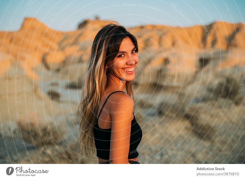 Delighted woman enjoying summer vacation in desert bardenas reales traveler sunset tourism valley dry female spain sunlight nature happy young carefree smile