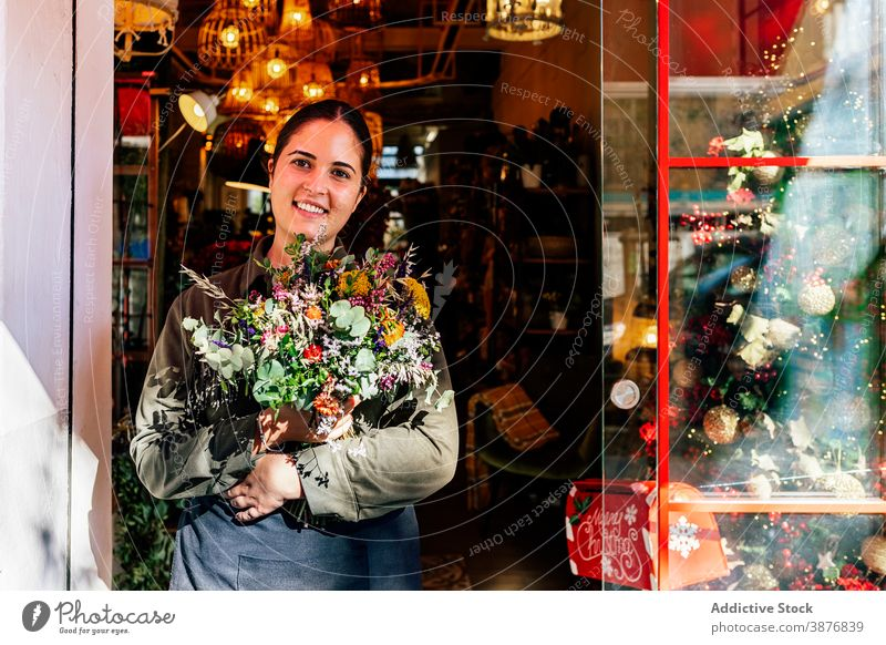 Woman with flower bouquet standing outside shop woman holiday window christmas store festive illumination xmas florist bloom street city celebration ornaments