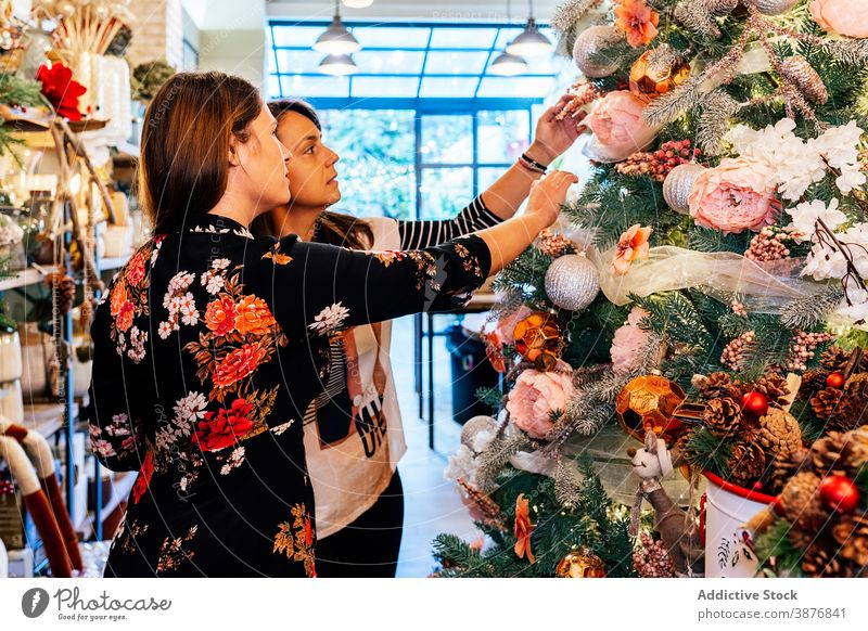 Mature female friends buying christmas ornaments inside decor shop women home interior celebration adult people happiness xmas santa baubles store lights