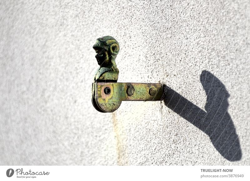 Galvanized shutter holder in the shape of a knight's head or a storm hood holder with swivel joint and two rivets in the holder is walled into a white house wall and casts a strong shadow in the sunlight