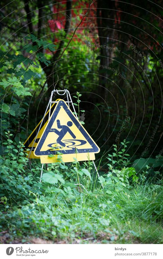 Warning sign for danger of slipping in the open air. bizarre and funny Slippery surface Nature Garden Signs and labeling Warning label Funny Exceptional bushes
