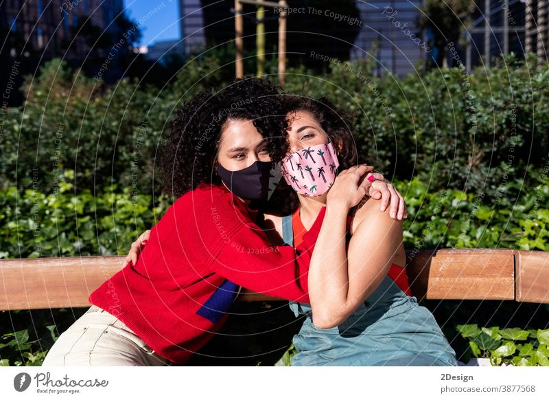 Lesbian couple with sunglasses embracing and relaxing on a park bench woman lesbian bonding person homosexual love lifestyle hug female mask coronavirus