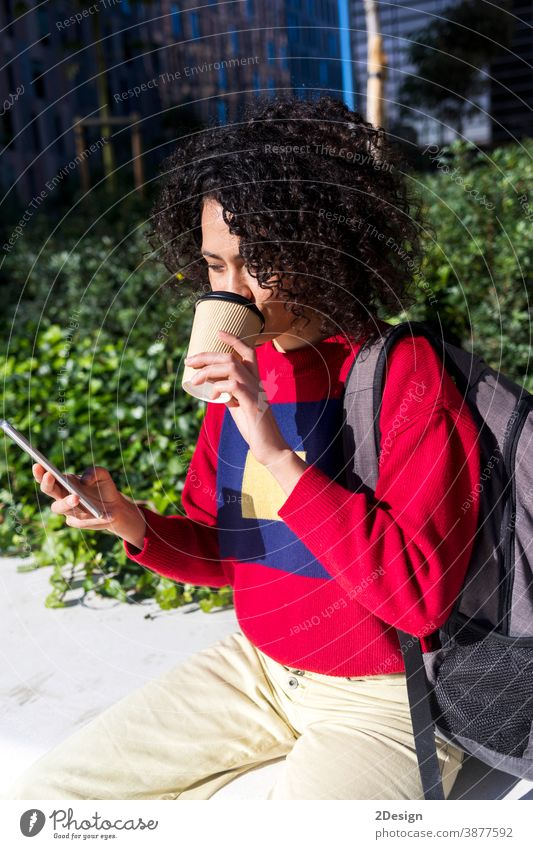 Beautiful young afro woman sitting on a bench outdoors, using mobile phone while drinking takeaway coffee cup smartphone take-away girl female backpack outside