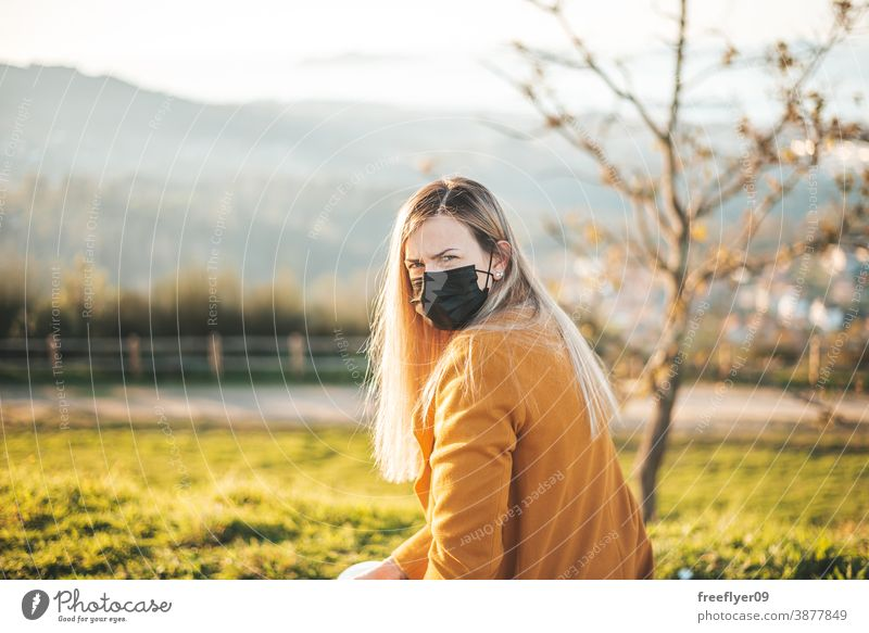 Woman on a yellow coat sitting on a bench with a face mask woman coronavirus covid winter autumn contemplating vigo galicia nature outdoors freedom sunset