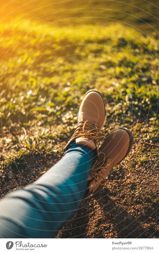 Detail of some feet relaxing boots woman grass copy space relaxation sunset hiking tourism tourist unrecognizable young rest morning dawn sunlight outdoors