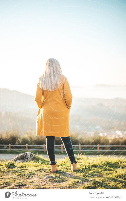 Woman on a yellow coat sitting on a bench contemplating the landscape woman winter autumn vigo galicia nature outdoors freedom sunset contemplation sky coolness