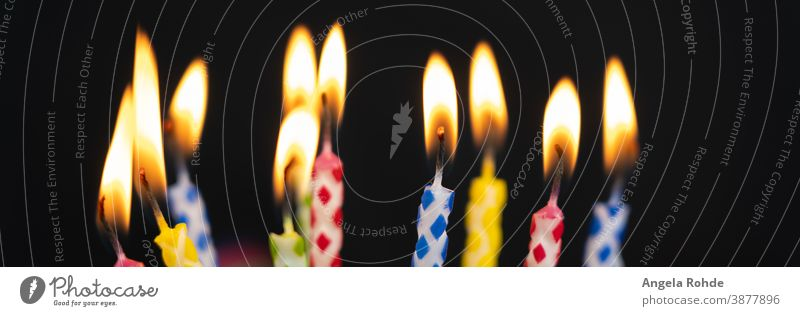 Many burning colourful birthday candles, black background with copy room Flame Fire cauterizing Black Birthday Party fun Anniversary Age shoulder stand
