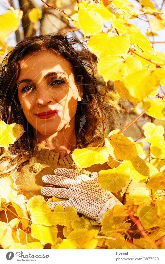 woman among yellow autumn leaves retouching hair park garden yellowish leafs lifestyle mature portrait one people tree coat yellow overcoat scene romantic