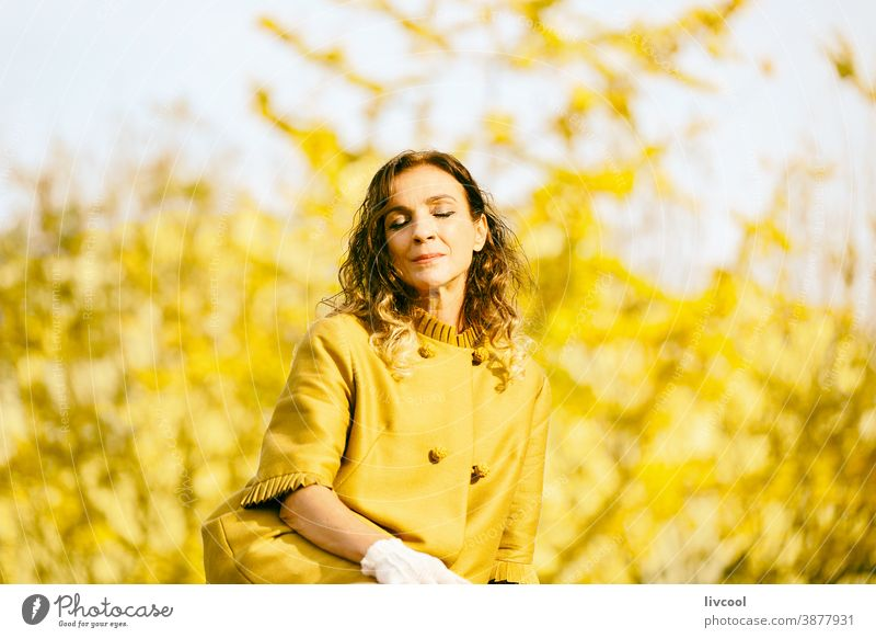 woman resting in the park during autumn retouching hair leaves yellow garden yellowish leafs lifestyle mature portrait one people tree coat yellow overcoat
