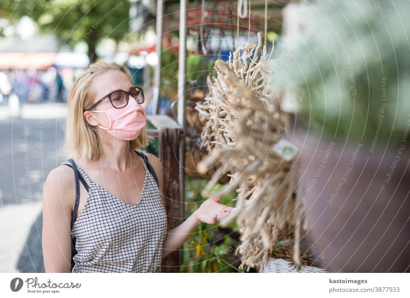 Casual woman shopping outdoor at open market stalls wearing fase masks for protection from corona virus pandemic in Munchen, Germany lifestyle outbreak