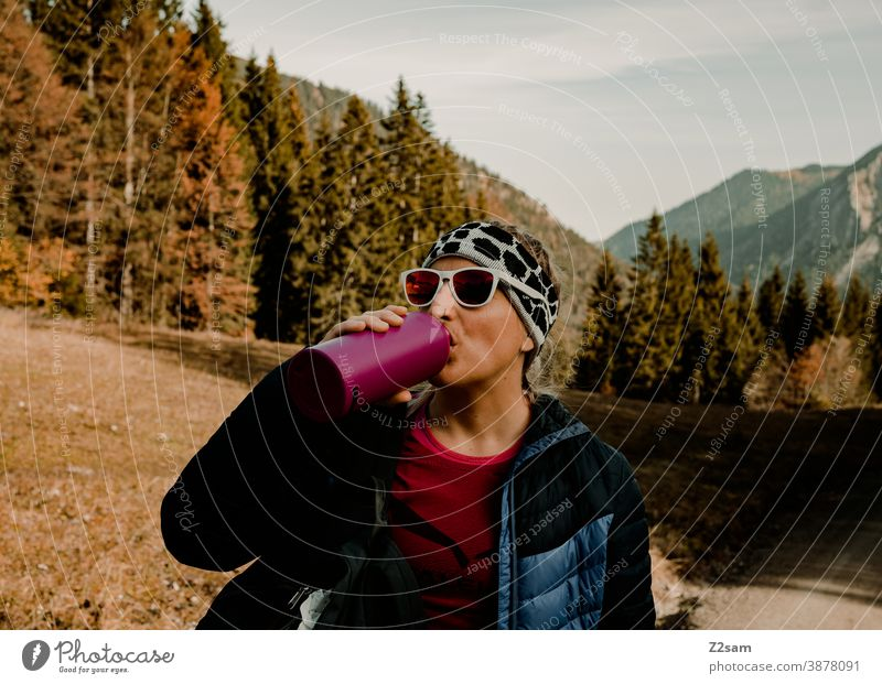 Young woman hiking drinks from a thermos bottle schliersee sharpened Hiking autumn colours Autumn Athletic outtdoor Backpack Trip Adventure Sports Movement