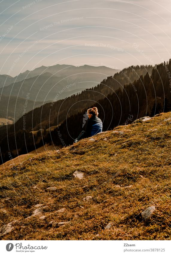 Young woman sitting on the summit of Spitzing in the Bavarian Alps schliersee sharpened Hiking autumn colours Autumn Athletic outtdoor Backpack Trip Adventure