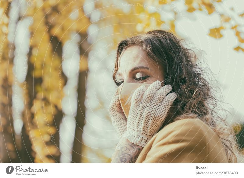 woman with gloves touching her mask yellow park garden yellowish leafs lifestyle mature portrait one people tree coat yellow overcoat scene romantic attitude