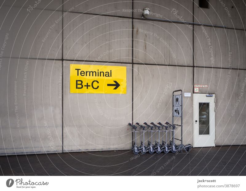 luggage trolleys, Terminal A, Tegel Airport direction arrow Wall (building) Road marking Cladding Signs and labeling door Orientation Symmetry Colorless