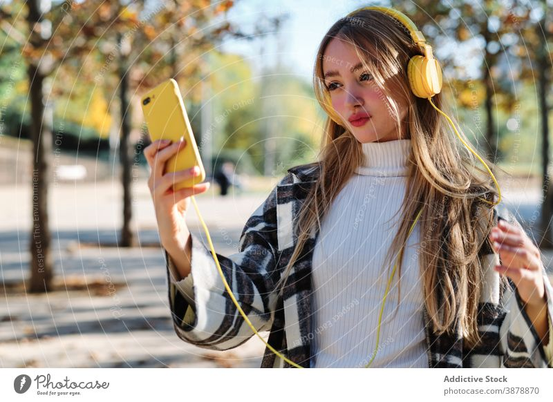 Trendy young woman with yellow headphones and smartphone in autumn park selfie using colorful trendy style millennial female checkered music listen wireless