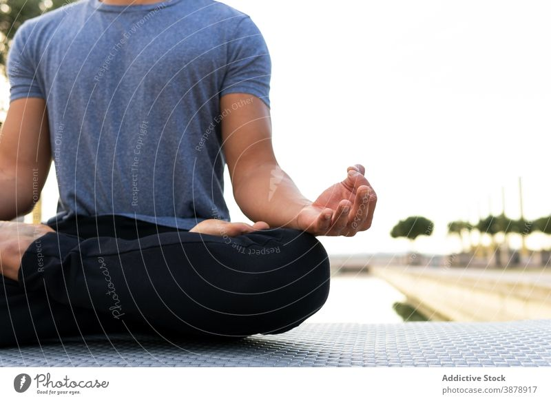 Tranquil man mediating in Lotus pose in park lotus pose meditate yoga harmony asana padmasana flexible legs crossed practice male mat relax calm balance sit