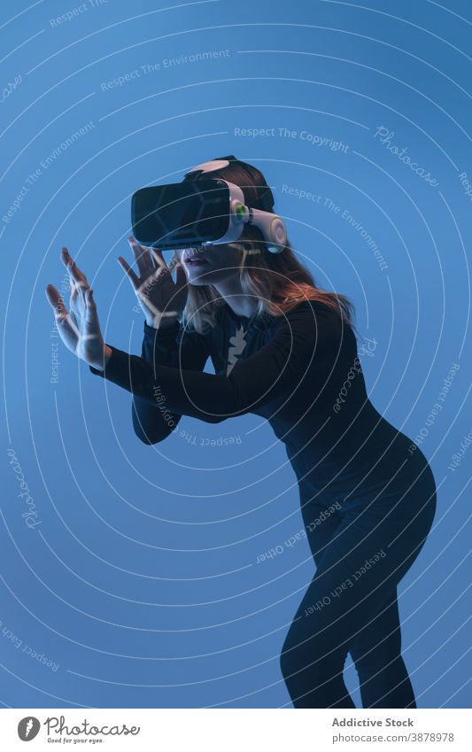 Anonymous young woman having VR experience vr headset technology device virtual reality modern innovation entertainment video futuristic simulation hi-tech