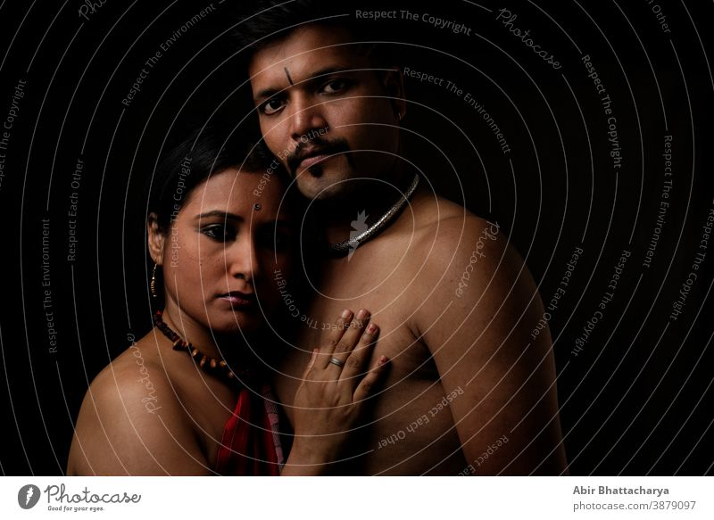 Creative portrait of an Indian dark brunette rural couple standing closely in studio light and shadow with black copy space background. Fashion portrait adult