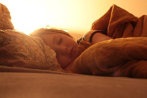 Child sleeps comfortably in bed asleep Bedtime Sleep Cozy evening light Warm colour eyes closed Dream Duvet Cushion Quilt Night light sleep well Bedroom Calm