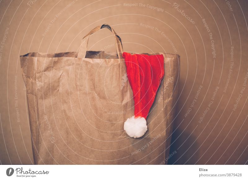 Paper bag with a Santa hat peeping out of it. Christmas shopping. Shopping Santa Claus hat paper bag shopping bag Santa's cap Brown Christmas hat Cap Red
