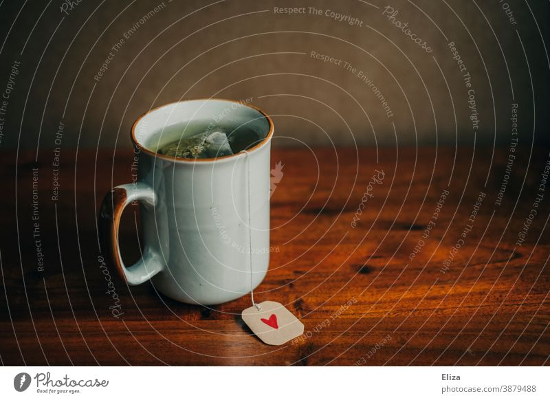 A cup with a tea bag and a small heart on the label. Drinking tea. Tea have tea Cup Tea cup Heart Label Cozy Warmth Wintertime get well well-being Mug Teatime