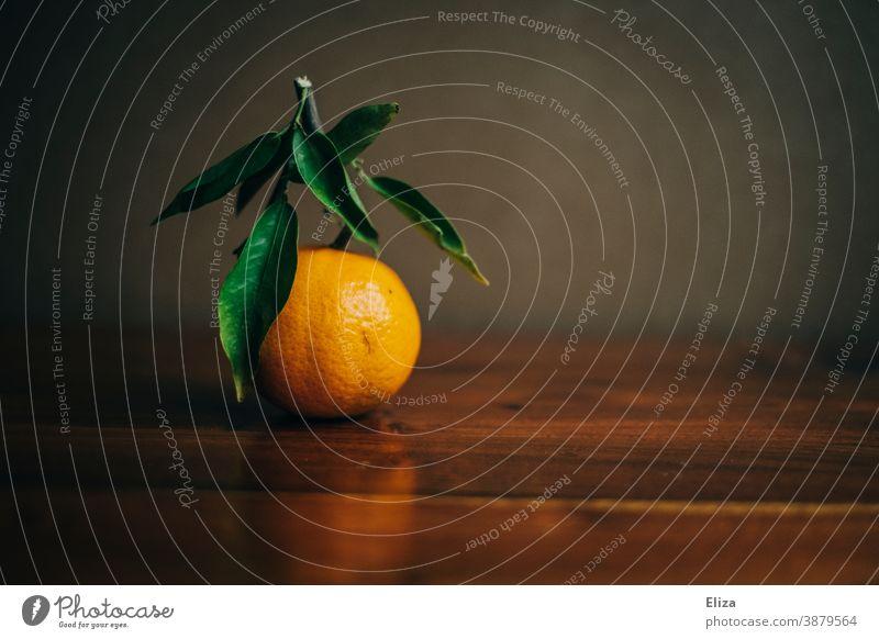 A tangerine with twig and leaves on wood Tangerine Citrus fruits clementine Orange Leaf Wood mandarins Twig Vitamin Winter Vitamin C