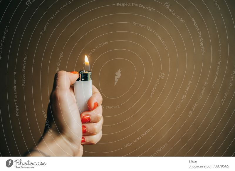 A female hand holds a burning lighter Lighter Burn Ignite Rousing Fire Flame Hand Hot Nail polish Kindle feminine Women`s hand Neutral Background Warmth