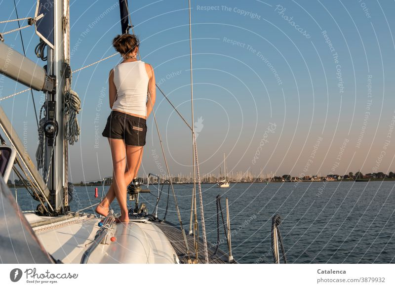 On this summer evening, the young woman stands port side ahead and looks at the marina on the horizon sailing yacht person feminine youthful Woman Stand Observe