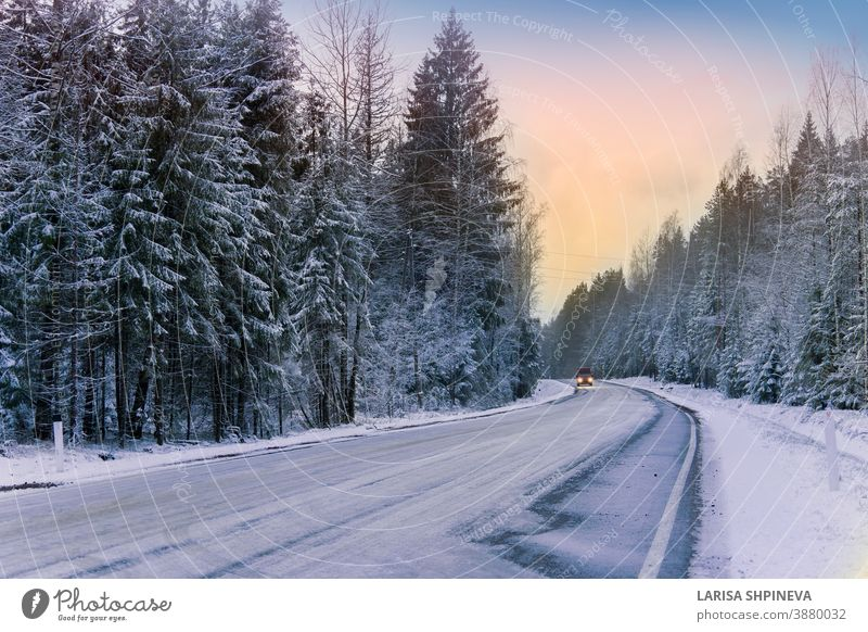Car drives on empty snowy road in winter forest. Beautiful frosty white landscape at dawn. season ice scene christmas tree day car freeze outdoor background