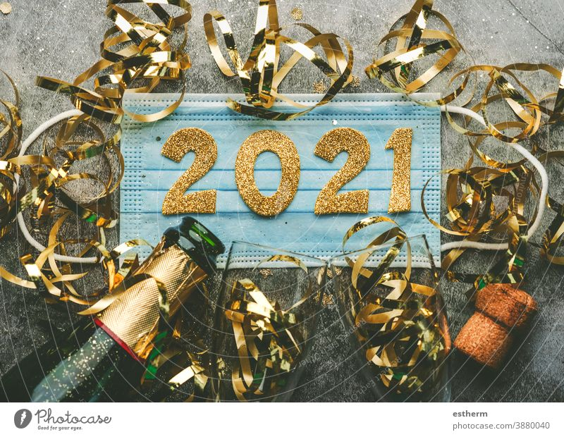 New Years Eve celebration concept background.Medical mask with the numbers 2021 and Champagne bottle with glasses .Covid-19 New Year concept christmas