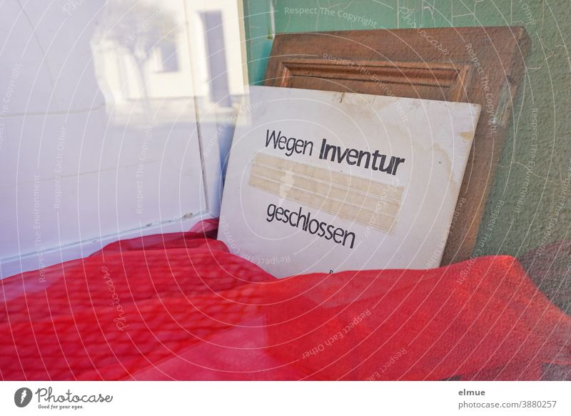 """Closed for inventory"" is written on a cardboard sign leaning against the wall in the empty shop window display covered with red cloth Inventory"