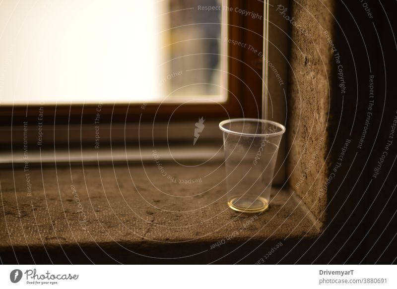 Abandoned empty plastic cup on a window sill glass waste litter littering thirsty copy space background drink transparent party recycle closeup blur nobody
