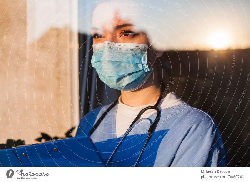 Young doctor looks through the window Anxious care clinic concerned Corona coronavirus COVID Cure dejected Diagnosis Doctor older emotionally Equipment Face