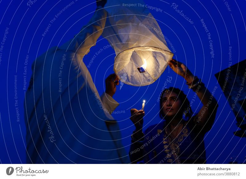An Indian Bengali couple is celebrating Diwali by lighting flying lanterns in the sky in blue hour. Indian lifestyle and Diwali celebration action active adult
