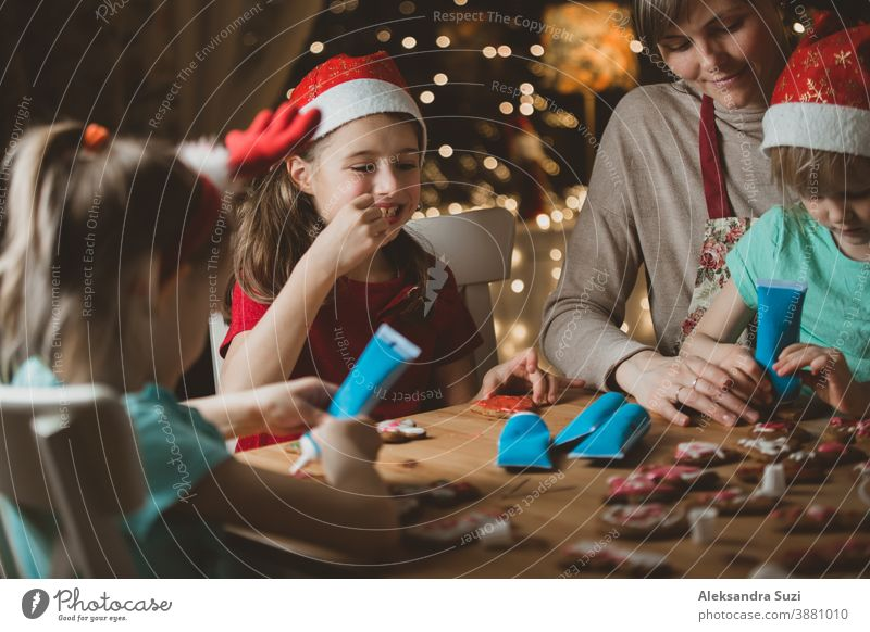 Mother and little kids in red hats cooking gingerbread cookies and decorating with glaze. Beautiful living room with lights and Christmas tree. Happy family celebrating holiday together.