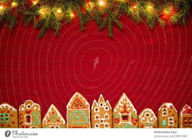 Christmas background. Red table cloth with town of cute gingerbread houses decorated with icing, Christmas lights, glitter. Holiday mood. building card