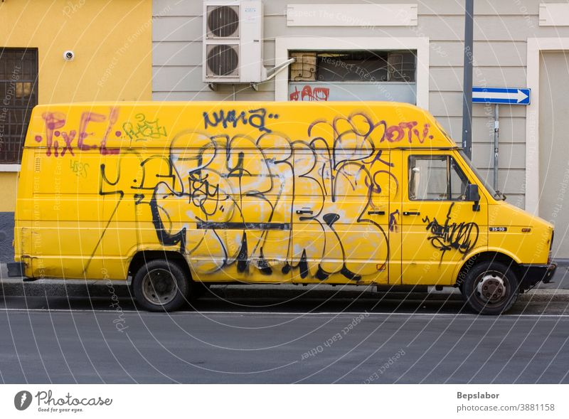 Yellow van covered with graffiti tag in the Milan street pick up yellow asphalt auto back background big blank business car cargo carrier container country