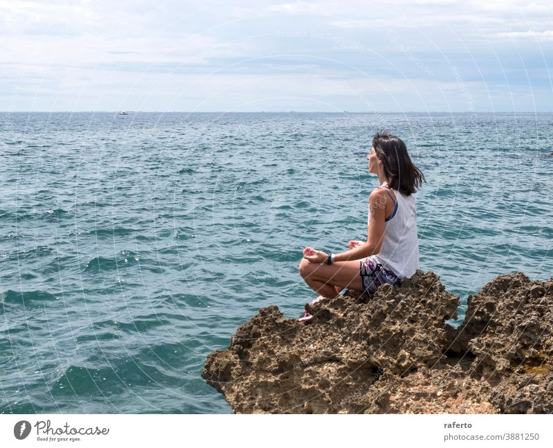 Beautiful woman practicing yoga on the beach at sunrise sitting rock water ocean sea beautiful holiday person girl female lifestyle nature one horizon calm